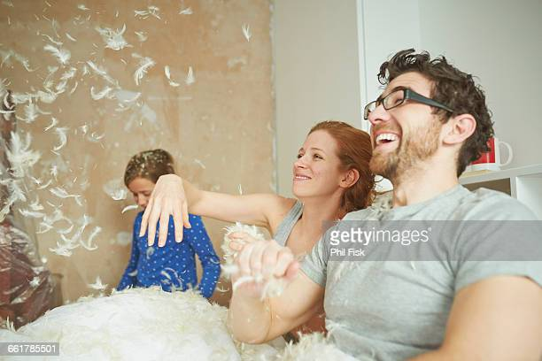 Mid adult couple pillow fighting daughter in bed