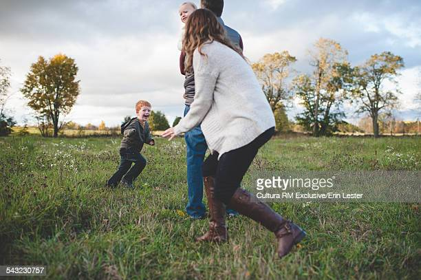 Mid adult couple playing chase with two young children in field