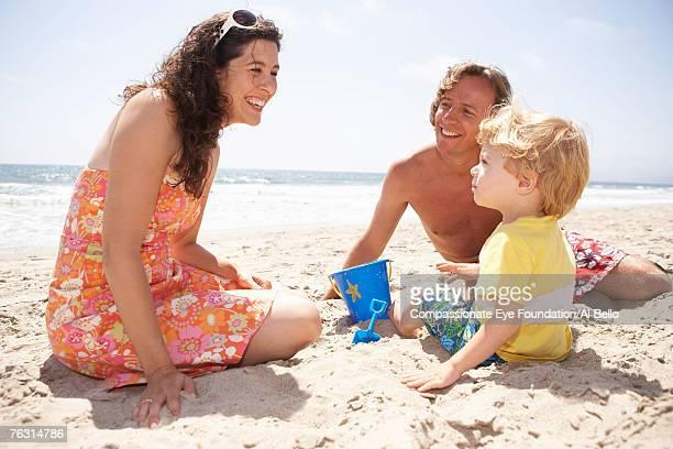mid adult couple playing with son (2-3) on beach - cef - fotografias e filmes do acervo