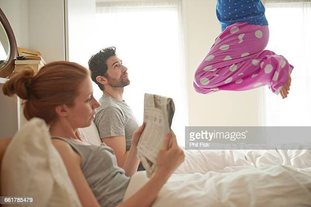 Mid adult couple reading broadsheet whilst daughter jumps on bed