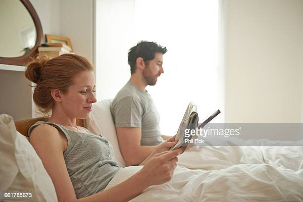Mid adult couple reading digital tablet and broadsheet in bed