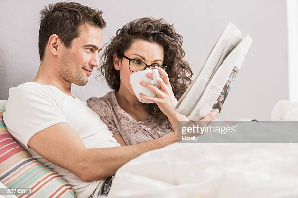 Mid adult couple reading newspaper in bed, drinking coffee