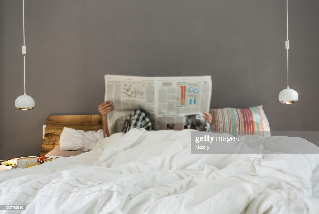 Mid adult couple reading newspaper in bed, faces obscured : Stock Photo