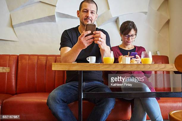 Mid adult couple reading smartphone texts in restaurant