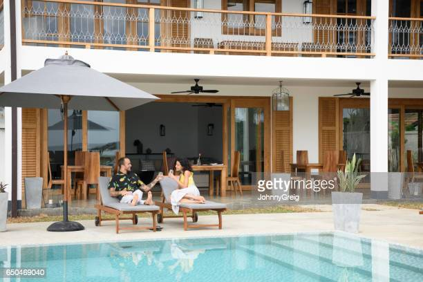 Mid adult couple reclining on sun loungers at the poolside