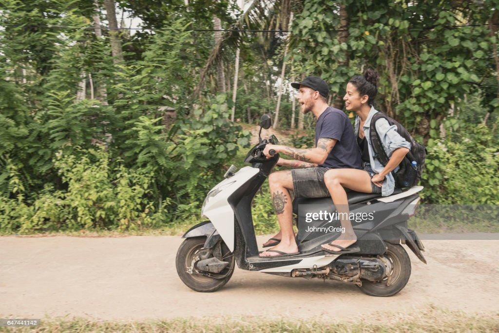 Mid adult couple riding moped through forest, side view : Stock Photo