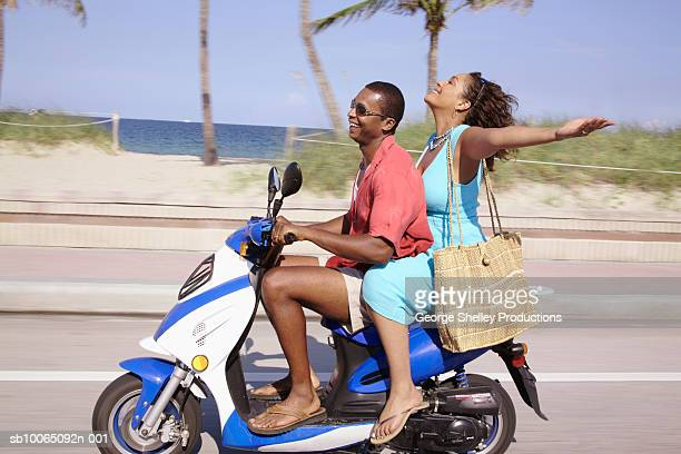 Mid adult couple riding motor scooter, woman with outstretched arms