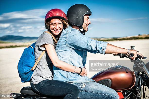 Mid adult couple riding motorcycle on arid plain, Cagliari, Sardinia, Italy