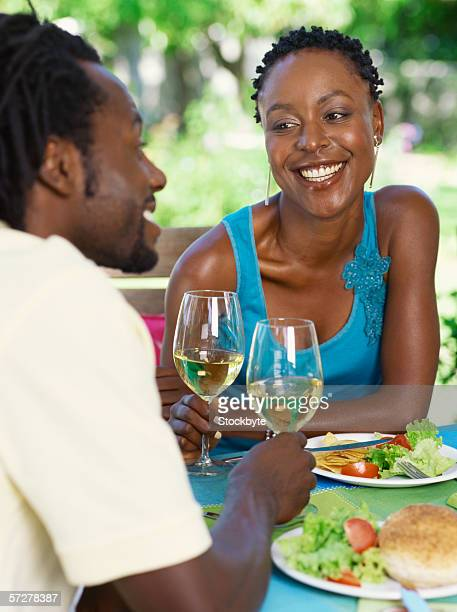 Mid adult couple sitting at a table holding glasses of white wine