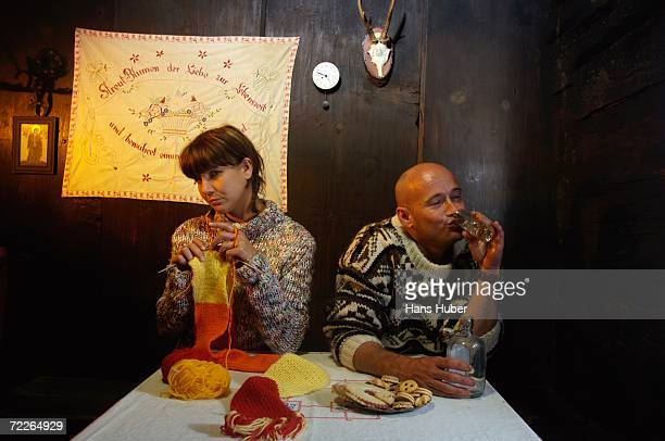 mid adult couple sitting by table in alpine hut - bad bangs stock pictures, royalty-free photos & images