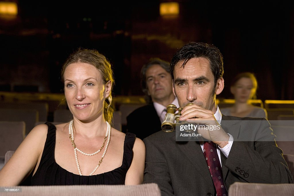 A mid adult couple sitting in a theater : Stock Photo