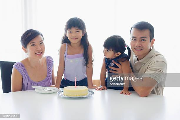 Mid adult couple sitting in front of a birthday cake with their two daughters