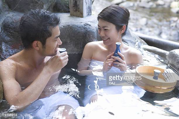 Mid Adult Couple Sitting in the Outdoor Hot Spring Bath, Drinking Sake, Front View, Side View