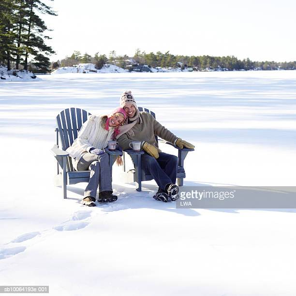 Mid adult couple sitting on chair in snow, smiling