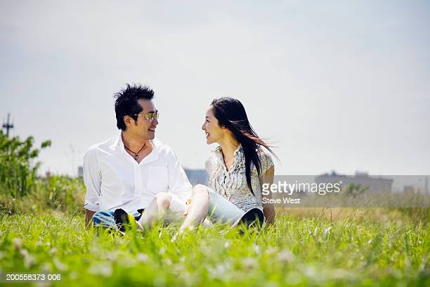 Mid adult couple sitting on grass, smiling