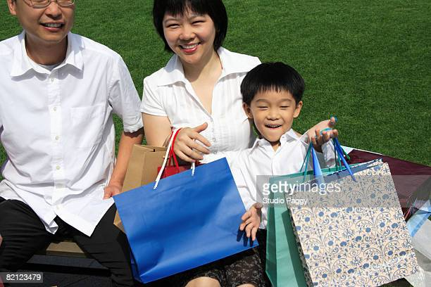 Mid adult couple sitting on the bench with their son in a park