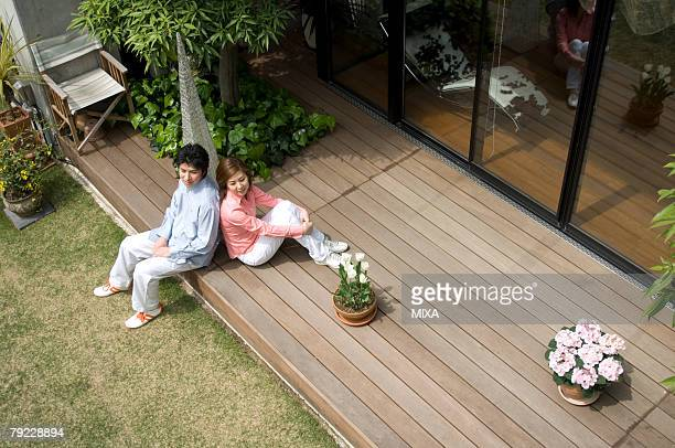 Mid adult couple sitting on wooden deck