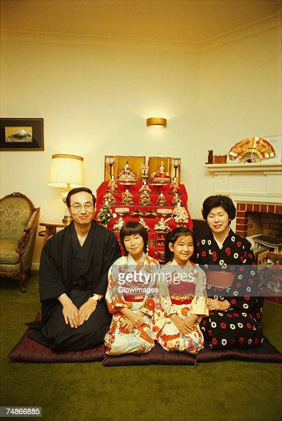 mid adult couple sitting with their two daughters in front of dolls at a traditional doll festival, hinamatsuri, tokyo prefecture, japan - hinamatsuri stock pictures, royalty-free photos & images