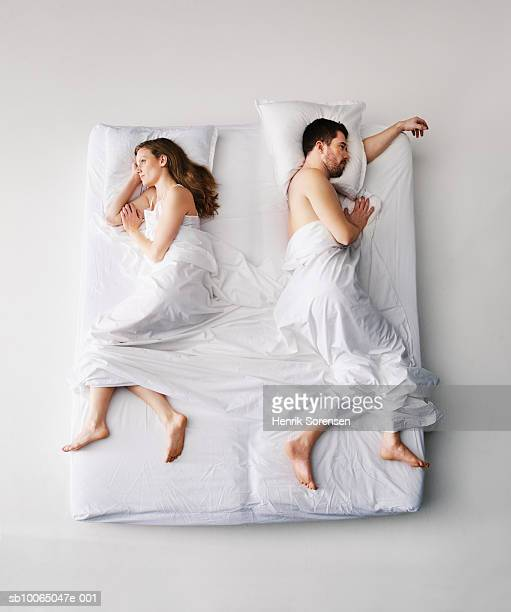 Mid adult couple sleeping in bed, elevated view