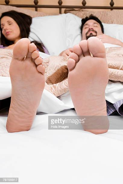 Mid adult couple sleeping on the bed