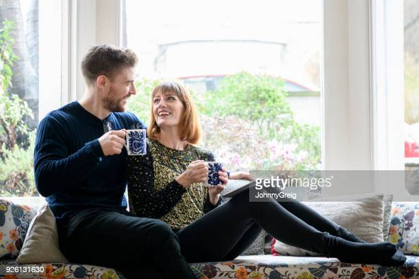mid adult couple smiling face to face and relaxing on sofa in window - 30 39 years stock pictures, royalty-free photos & images