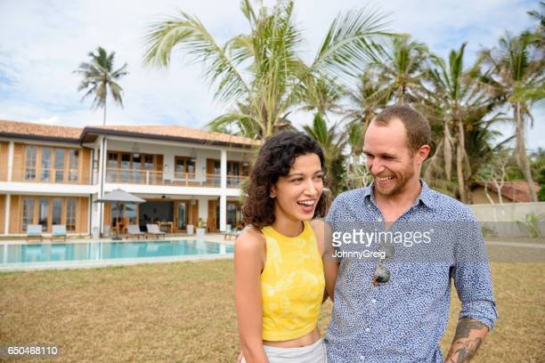 Mid adult couple smiling with luxury apartment in background