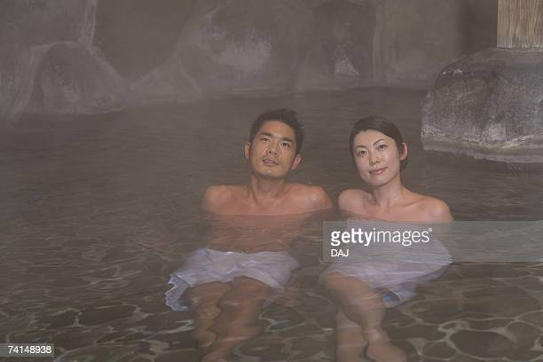 mid adult couple soaking in the outdoor hot spring bath together, front view - 温泉 ストックフォトと画像