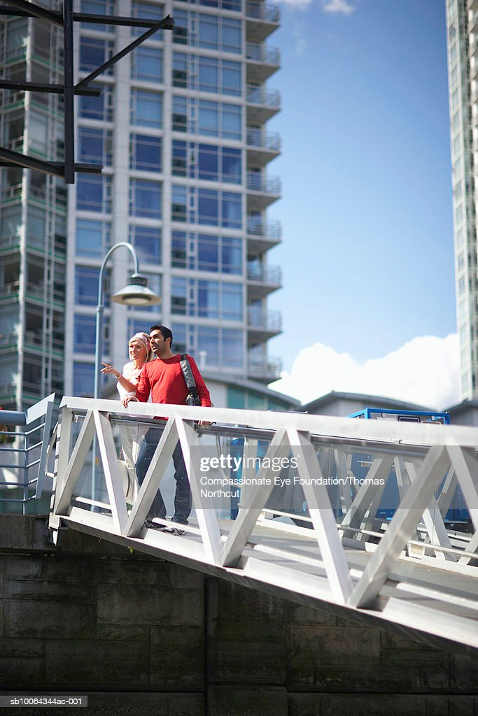Mid adult couple standing on bridge looking at view : Stock Photo