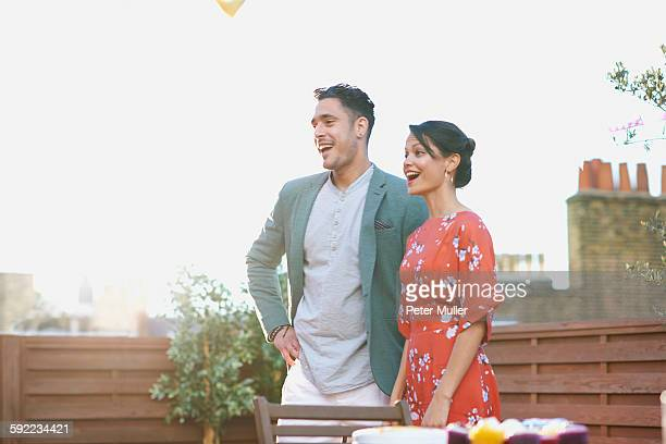 Mid adult couple standing on roof terrace looking away smiling, mouth open
