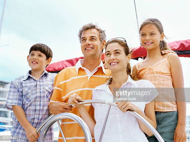 mid adult couple steering a sailboat with their children and smiling - bang boat stock pictures, royalty-free photos & images