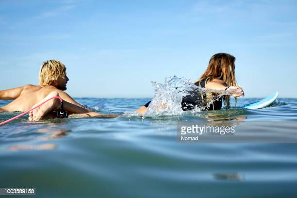 mid adult couple surfing in sea against sky - paddling stock pictures, royalty-free photos & images
