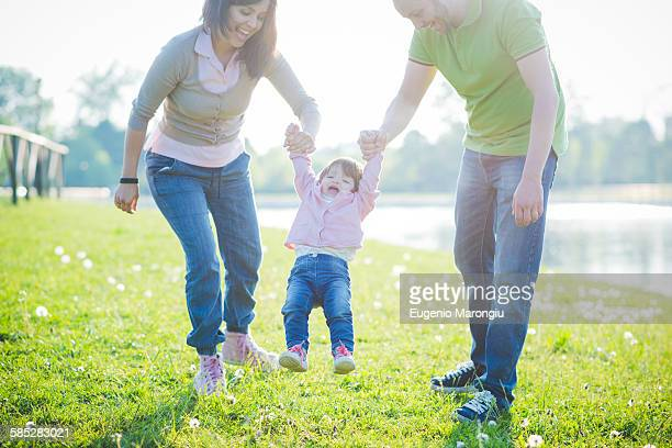 mid adult couple swinging toddler daughter in park - riverbank stock pictures, royalty-free photos & images