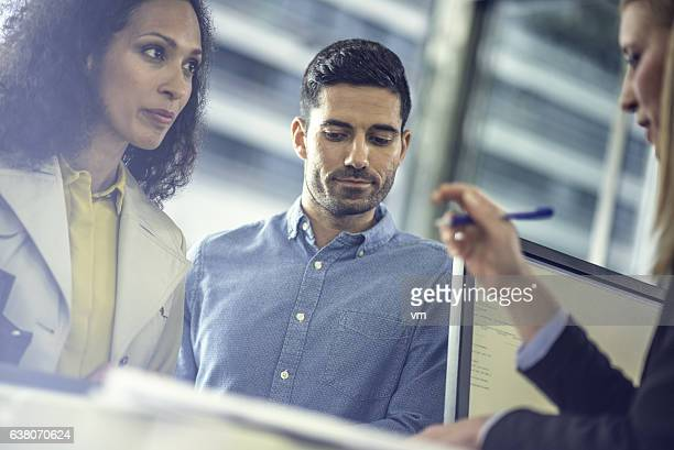 Mid adult couple talking to travel agent