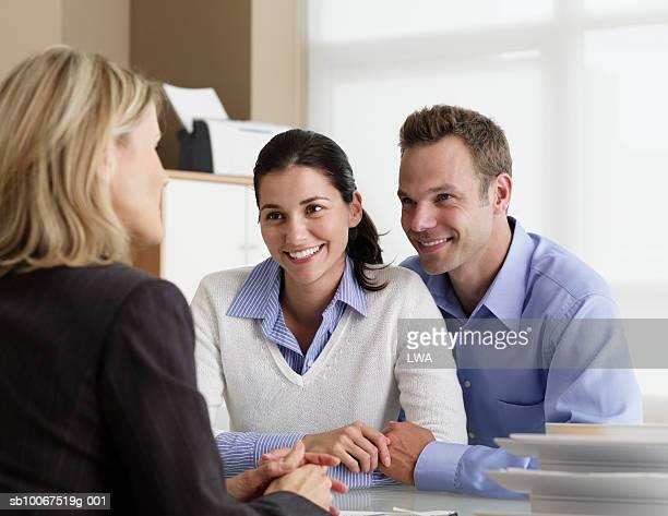 mid adult couple talking with insurance agent in office, smiling - versicherung stock-fotos und bilder