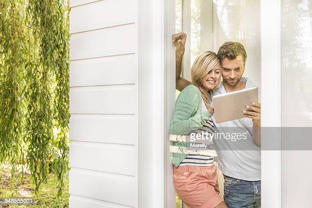 Mid adult couple using digital tablet at house window