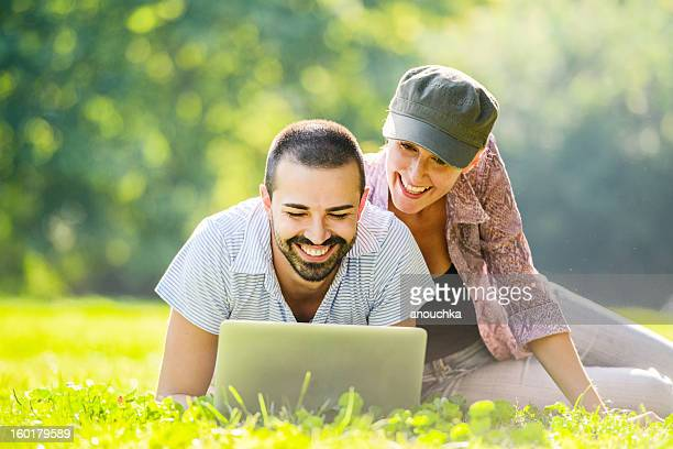 Mid Adult couple using laptop  outdoors