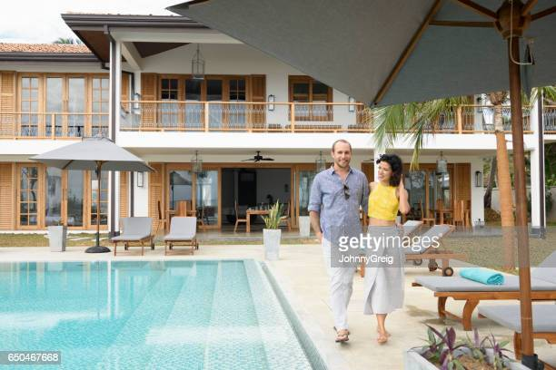 Mid adult couple walking next to swimming pool on vacation
