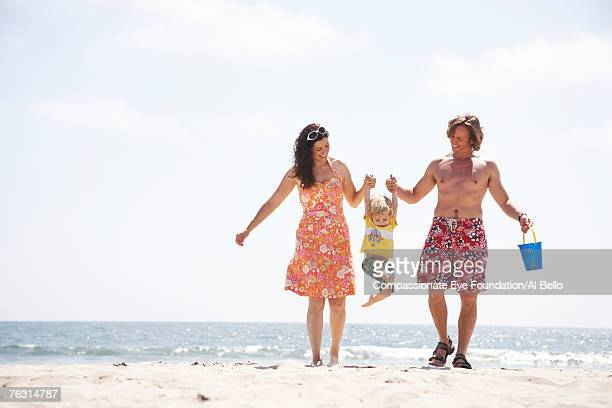 mid adult couple walking on beach, carrying son (2-3) in air - cef - fotografias e filmes do acervo