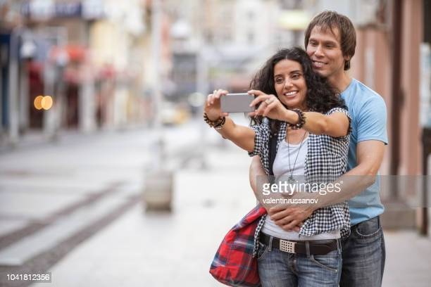 Mid adult couple walking on street and taking selfie