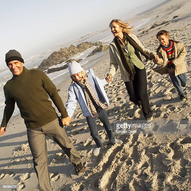 mid adult couple walking on the beach with their children - 子供2人の家庭 ストックフォトと画像