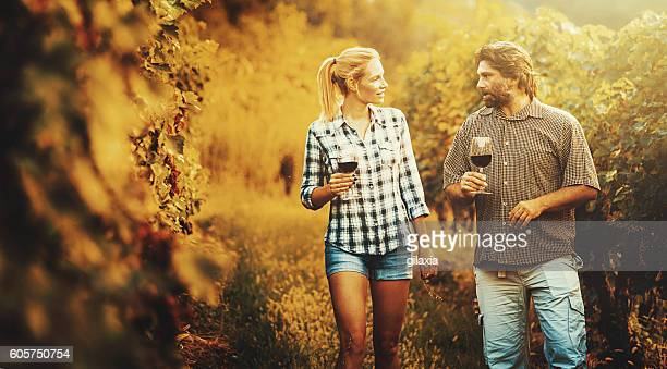 Mid adult couple walking through a vineyard.