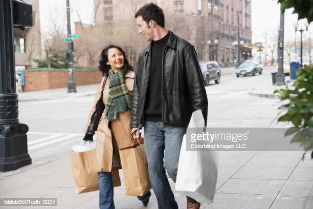 mid adult couple walking with shopping bags - overcoat stock pictures, royalty-free photos & images