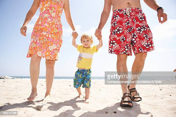 mid adult couple walking with son (2-3) on beach, low section - cef - fotografias e filmes do acervo