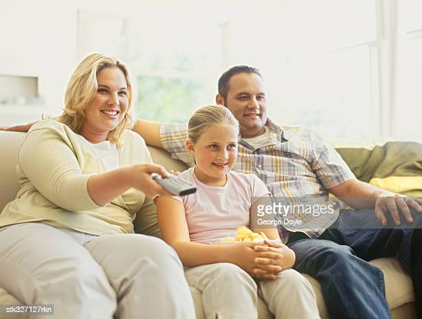mid adult couple watching television with their daughter