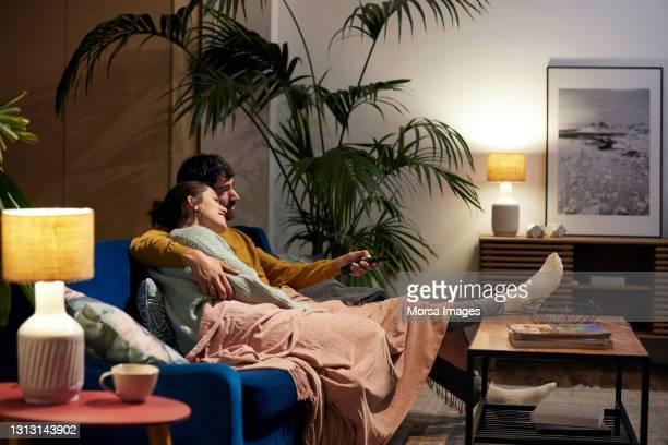mid adult couple watching tv in living room - dos personas fotografías e imágenes de stock
