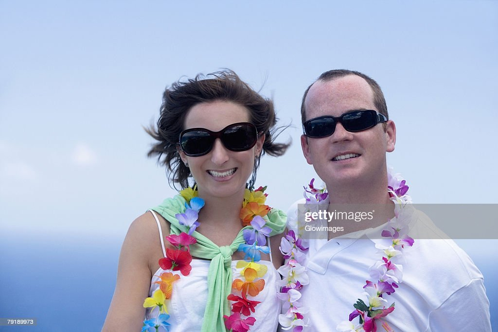 Mid adult couple wearing garlands and smiling : Foto de stock