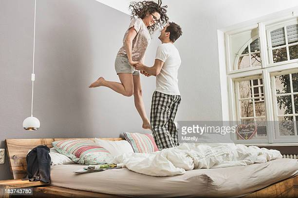 mid adult couple wearing pyjamas jumping on bed - lit ameublement photos et images de collection