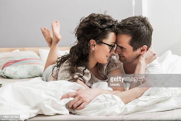 mid adult couple wearing pyjamas lying on front on bed, face to face - after party mess stock pictures, royalty-free photos & images
