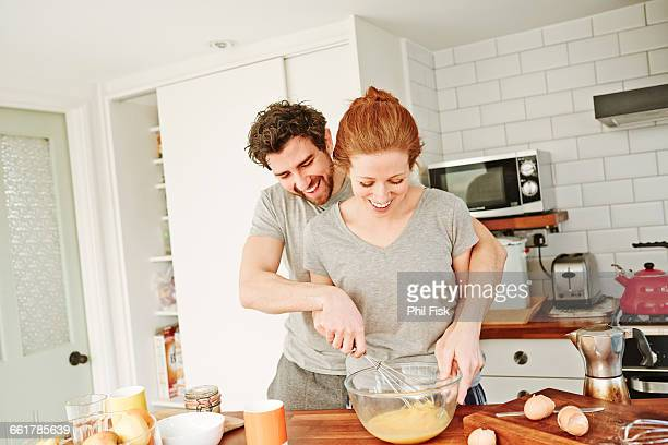 mid adult couple whisking eggs together at kitchen counter for breakfast - women whipping men stock photos and pictures