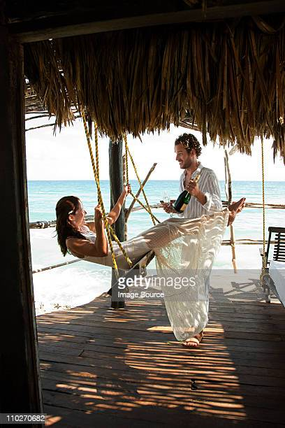 mid adult couple with champagne, woman on swing - maxi dress stock pictures, royalty-free photos & images